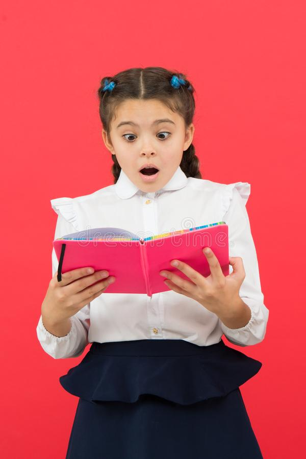 Ποιες ειδήσεις μιας έκπληξης Έκπληκτο βιβλίο ανάγνωσης κοριτσιών στο κόκκινο υπόβαθρο Λατρευτός λίγο παιδί με την αιφνιδιαστική σ στοκ εικόνα με δικαίωμα ελεύθερης χρήσης