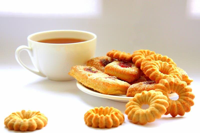 Ποικίλα διαμορφωμένα μπισκότα Άσπρο φλυτζάνι του τσαγιού Το πρωί είναι γλυκό   στοκ εικόνες