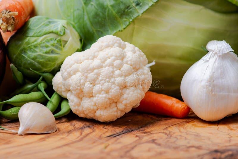 Ποικίλα φρέσκα ακατέργαστα οργανικά λαχανικά συμπεριλαμβανομένου του κόκκινου κρεμμυδιού, σκόρδο, γαλλικά πράσινα φασόλια, κουνου στοκ εικόνες