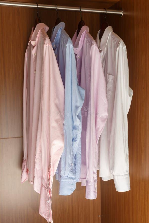 Ποικιλία των πουκάμισων ατόμων ` s ξύλινες κρεμάστρες στοκ εικόνες με δικαίωμα ελεύθερης χρήσης