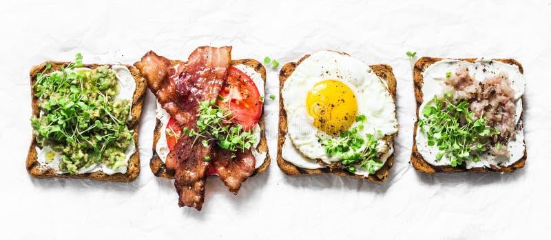 Ποικιλία των σάντουιτς για το πρόγευμα, πρόχειρο φαγητό, ορεκτικά - ο πουρές αβοκάντο, τηγάνισε το αυγό, ντομάτες, μπέϊκον, τυρί, στοκ φωτογραφίες