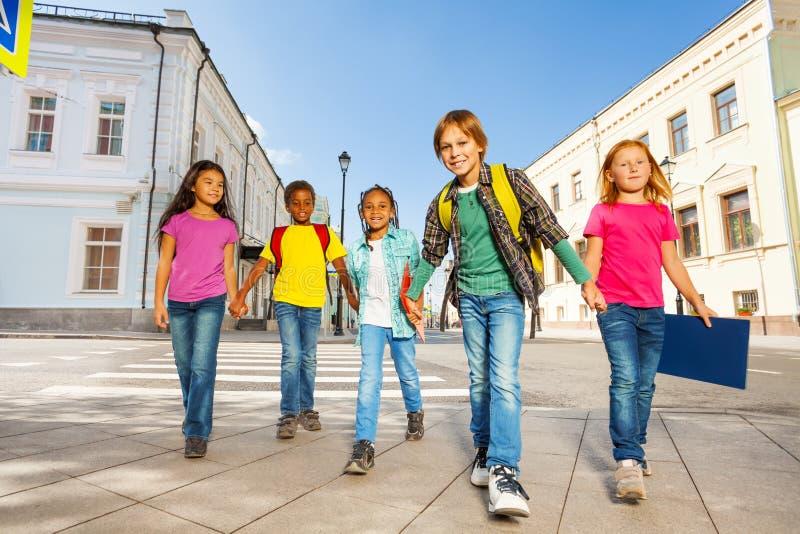 Ποικιλομορφία παιδιών που περπατά μαζί να κρατήσει τα χέρια στοκ φωτογραφίες