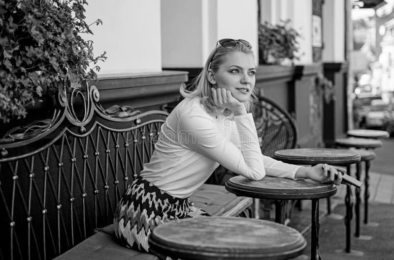 Ποιοι εάν καλούσα Το περίεργο πρόσωπο γυναικών κάθεται με το αστικό υπόβαθρο πεζουλιών καφέδων smartphone Κυρία που ψάχνει την επ στοκ εικόνες
