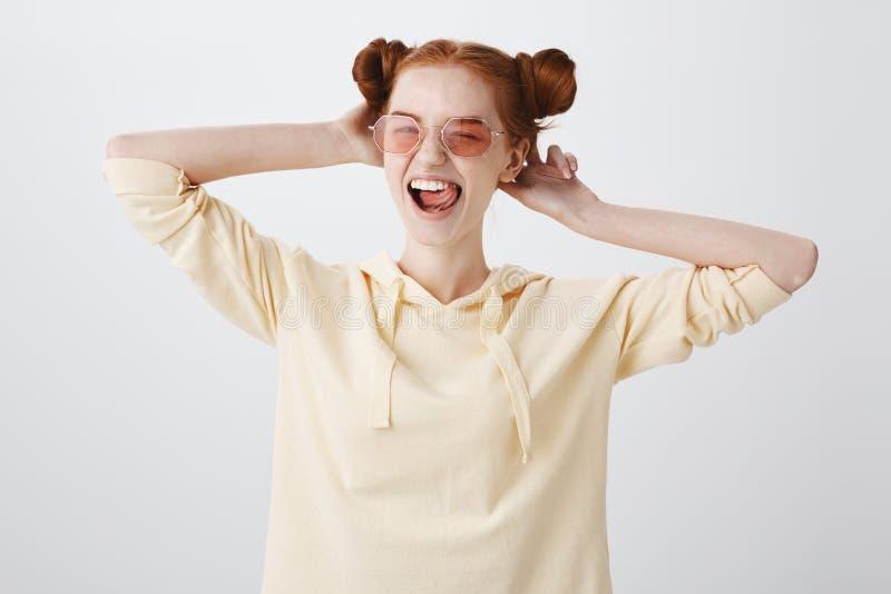 Ποιος συμπαθητικός χρόνος να είναι ζωντανός Συγκινητικό ευτυχές νέο κορίτσι με την κόκκινη τρίχα και κουλούρια στα ρόδινα μοντέρν στοκ φωτογραφία