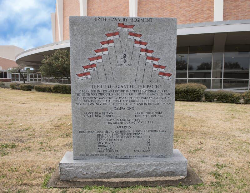 Πολεμικό μνημείο στο 112ο σύνταγμα Calvary στον αναμνηστικό κήπο παλαιμάχων με την αναμνηστική αίθουσα συνεδριάσεων του Ντάλλας σ στοκ φωτογραφία με δικαίωμα ελεύθερης χρήσης