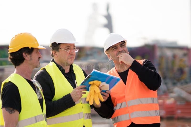 Πολιτικοί μηχανικοί στην εργασία για το εργοτάξιο οικοδομής στοκ φωτογραφίες