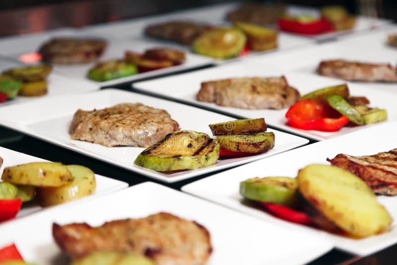 Πολλά άσπρα κεραμικά τετραγωνικά πιάτα με τις ψημένες στη σχάρα μπριζόλες κρέατος και ομο στοκ φωτογραφία με δικαίωμα ελεύθερης χρήσης