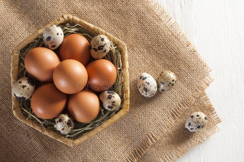 Πολλά διαφορετικά αυγά στο καλάθι και burlap άσπρος ξύλινος ανασκόπησης στοκ εικόνες