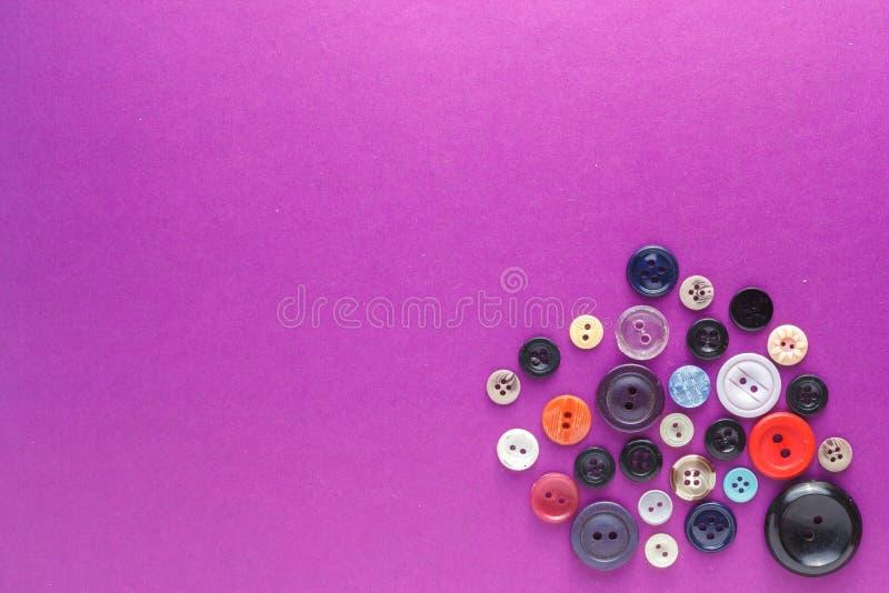 Πολλά διαφορετικά κουμπιά σε ένα πορφυρό υπόβαθρο στοκ φωτογραφία