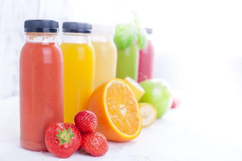 Πολλά διαφορετικά φρούτα και μούρα και χυμοί στα πλαστικά μπουκάλια Καρπούζι, μπανάνα, applcsin, βακκίνια, φράουλες, βασιλικός επ στοκ φωτογραφίες