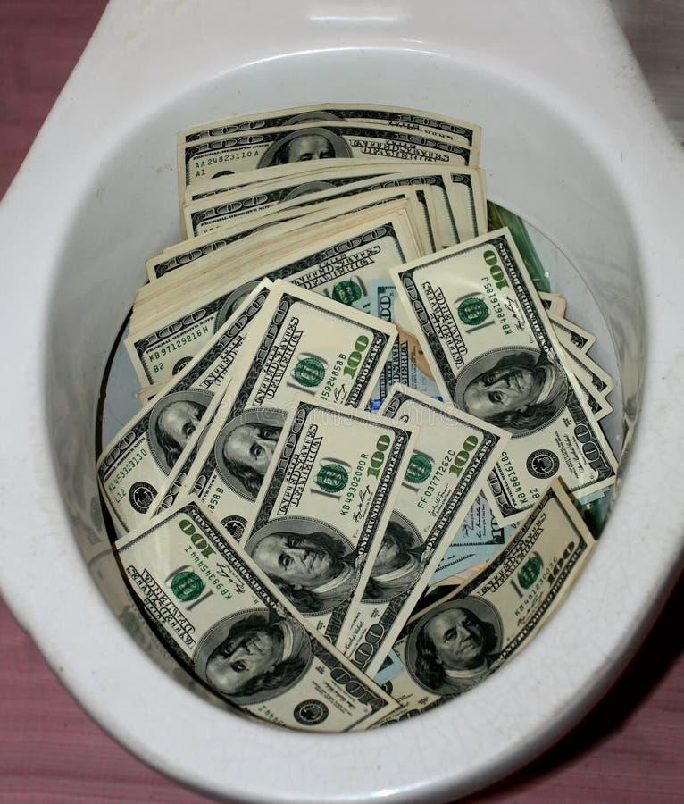 Πολλά δολάρια σε ένα κύπελλο τουαλετών Τουαλέτα χρημάτων στοκ φωτογραφία με δικαίωμα ελεύθερης χρήσης