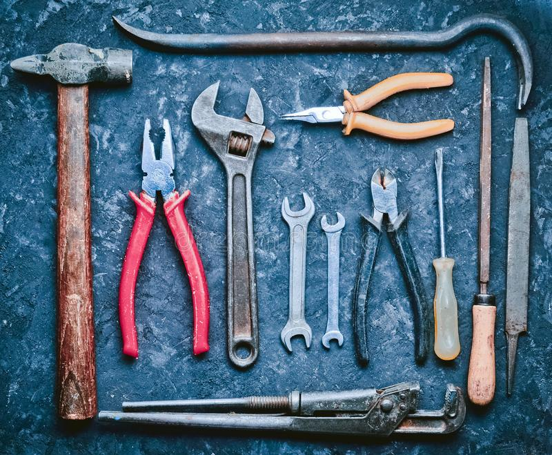 Πολλά εργαλεία εργασίας σε έναν μαύρο συγκεκριμένο πίνακα Nippers, αρχείο, pli στοκ εικόνες