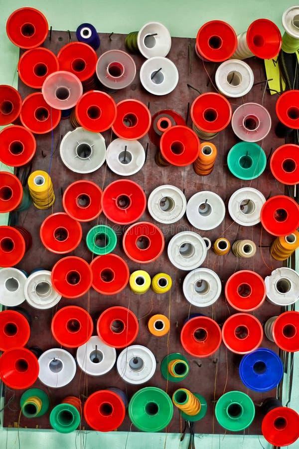 Πολλά ζωηρόχρωμα στροφία του νήματος σε ένα ράβοντας εργαστήριο στοκ εικόνες