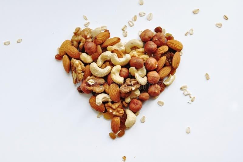 Πολλά καρύδια, που χύνονται διαφορετικά υπό μορφή καρδιάς στοκ φωτογραφία