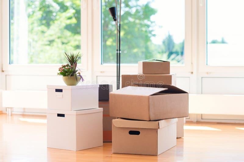 Πολλά κουτιά από χαρτόνι στο φωτεινό σπίτι κατά τη διάρκεια του επανεντοπισμού στοκ εικόνα με δικαίωμα ελεύθερης χρήσης