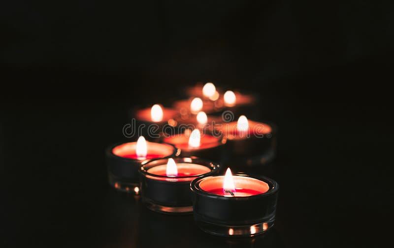 Πολλά κόκκινα κεριά άναψαν στο σκοτάδι με το bokeh Σκοτεινός και ευμετάβλητος αισθανθείτε στοκ φωτογραφία