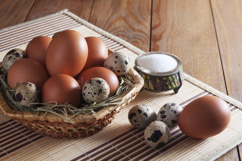 Πολλά μεγάλα καφετιά αυγά κοτόπουλου και μικρά ετερόκλητα αυγά ορτυκιών στο καλάθι επάνω από την όψη στοκ εικόνα
