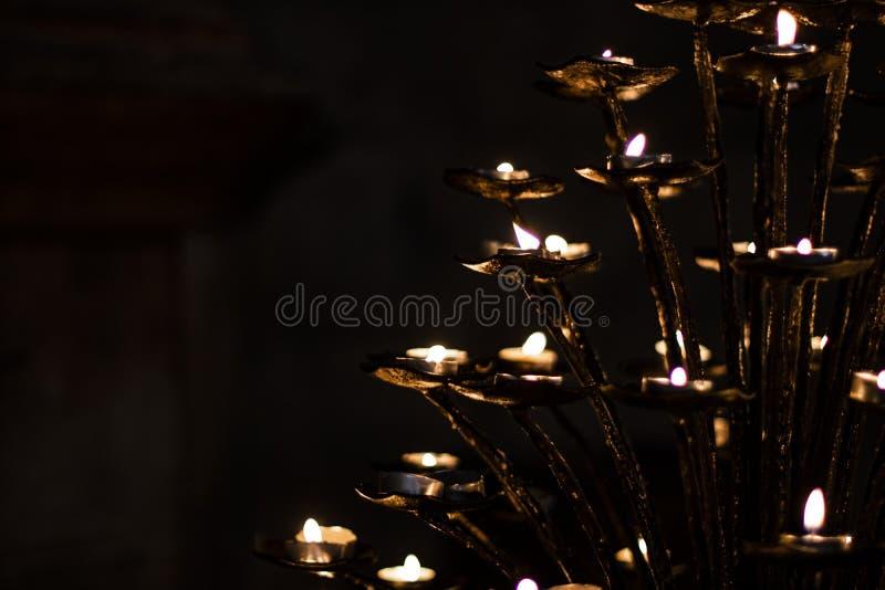 Πολλά μικρά επίκεντρα κεριών σε ένα σκοτεινό μαύρο υπόβαθρο στοκ φωτογραφία με δικαίωμα ελεύθερης χρήσης