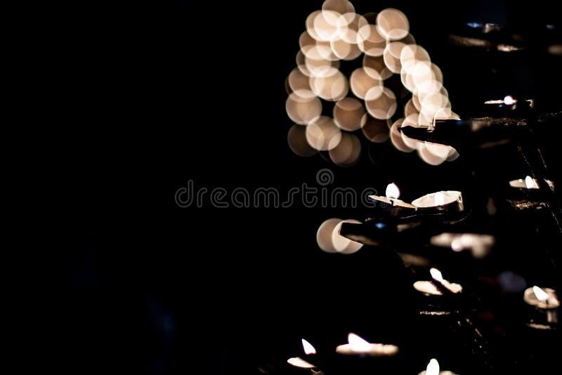 Πολλά μικρά κεριά που φλέγονται τα επίκεντρα σε ένα σκοτεινό μαύρο υπόβαθρο στοκ εικόνες με δικαίωμα ελεύθερης χρήσης