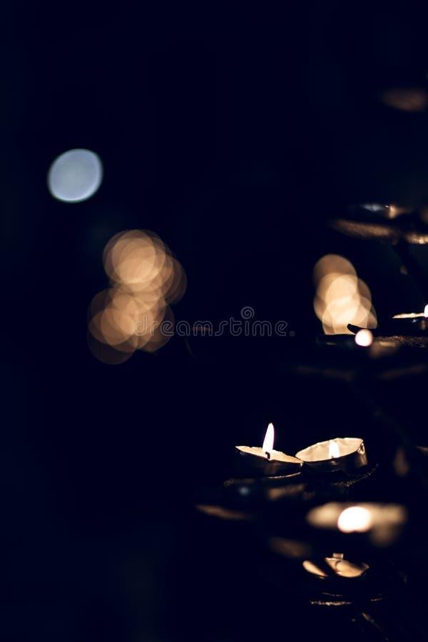 Πολλά μικρά κεριά που φλέγονται τα επίκεντρα σε ένα σκοτεινό μαύρο υπόβαθρο στοκ φωτογραφίες με δικαίωμα ελεύθερης χρήσης