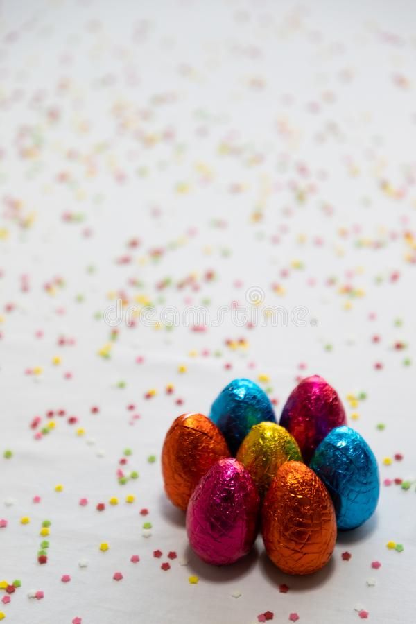 Πολλά μόνιμα χρωματισμένα αυγά Πάσχας σοκολάτας στο άσπρο υπόβαθρο και το ζωηρόχρωμο κομφετί στοκ φωτογραφίες