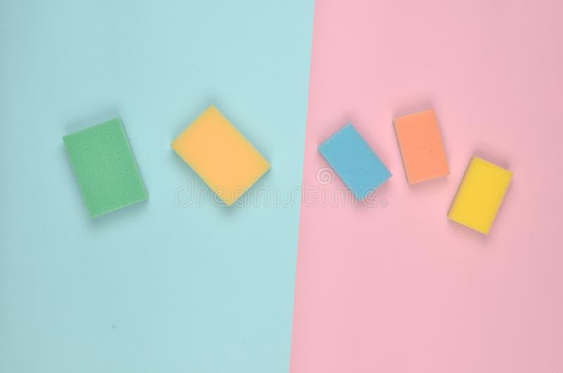 Πολλά πολύχρωμα σφουγγάρια για τον καθαρισμό σε ένα ρόδινο μπλε υπόβαθρο κρητιδογραφιών Τάση του μινιμαλισμού Τοπ όψη στοκ φωτογραφίες με δικαίωμα ελεύθερης χρήσης