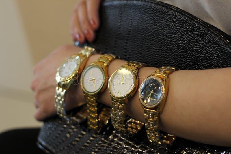 Πολλά ρολόγια το κορίτσι έχουν σε ετοιμότητα της ένα χρυσό ρολόι στοκ φωτογραφίες