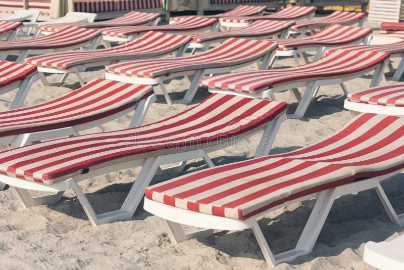 Πολλά σαλόνια μονίππων με τα στρώματα με τα κόκκινα λωρίδες στέκονται στην άμμο στην παραλία, η έννοια του ταξιδιού στοκ φωτογραφία με δικαίωμα ελεύθερης χρήσης