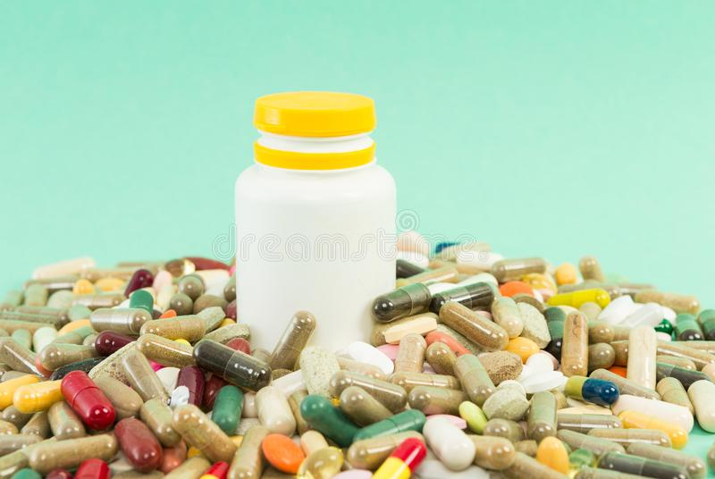 Πολλά τυχαία χάπια με τον πλαστικό παραλήπτη στοκ εικόνα με δικαίωμα ελεύθερης χρήσης