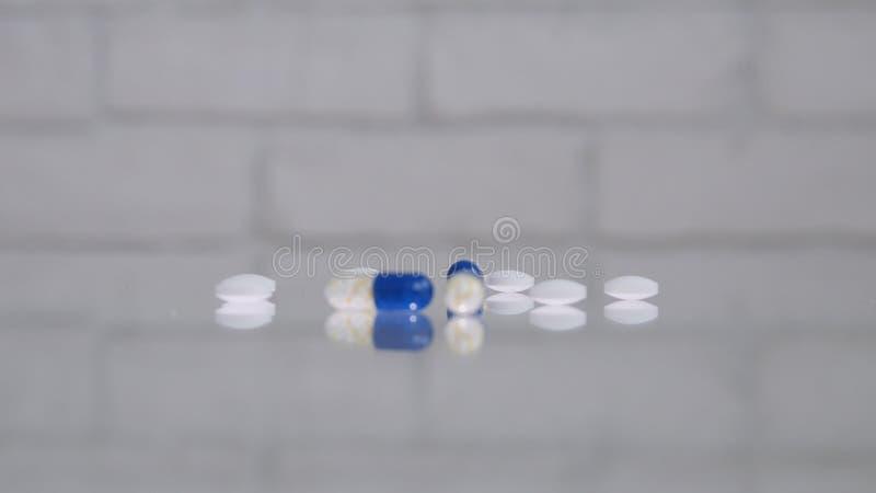 Πολλά χρωματισμένα χάπια στην επιτραπέζια διαφανή επιφάνεια στοκ εικόνες