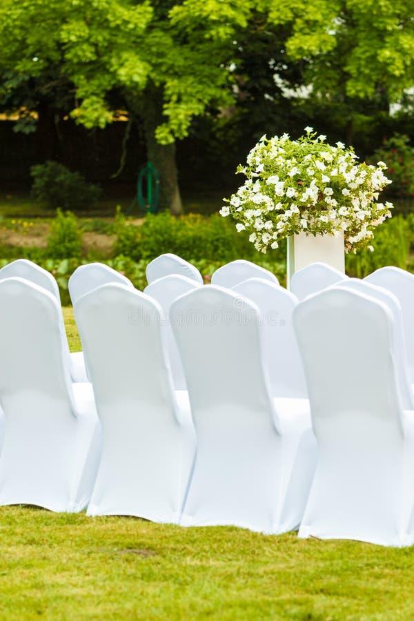 Πολλές γαμήλιες καρέκλες με τις άσπρες κομψές καλύψεις στοκ εικόνες