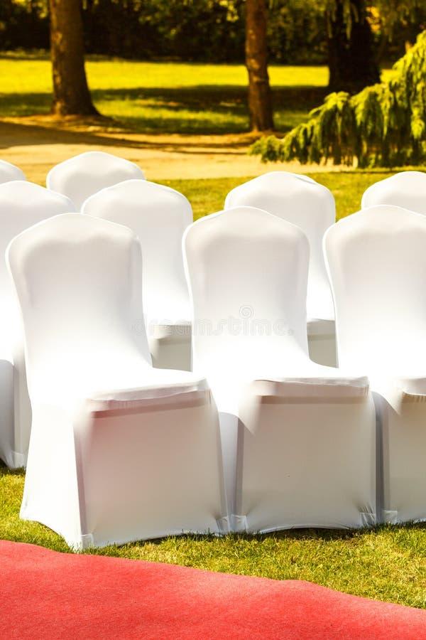 Πολλές γαμήλιες καρέκλες με τις άσπρες κομψές καλύψεις στοκ φωτογραφία με δικαίωμα ελεύθερης χρήσης