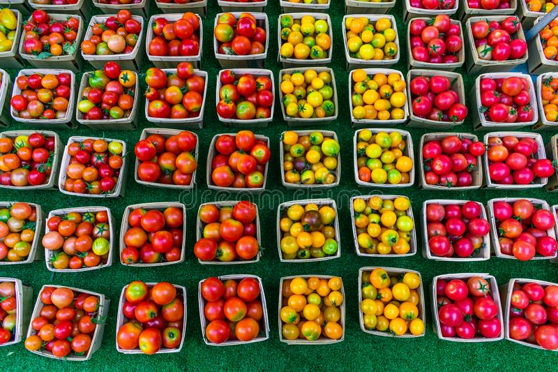 Πολλές ζωηρόχρωμες ντομάτες κερασιών για την πώληση σε μια αγορά αγροτών στοκ φωτογραφίες