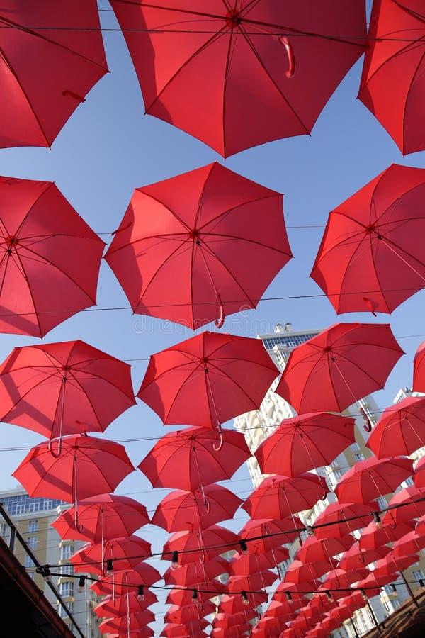 Πολλές κόκκινες ομπρέλες κοραλλιών ενάντια στο μπλε ουρανό Άποψη από κάτω από Αφηρημένο υπόβαθρο με τις κόκκινες ομπρέλες στοκ εικόνες
