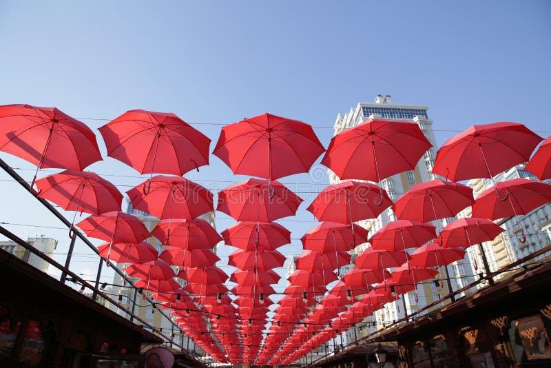 Πολλές κόκκινες ομπρέλες κοραλλιών ενάντια στο μπλε ουρανό και το φωτεινό κτήριο Αφηρημένο υπόβαθρο με τις ομπρέλες στοκ εικόνα