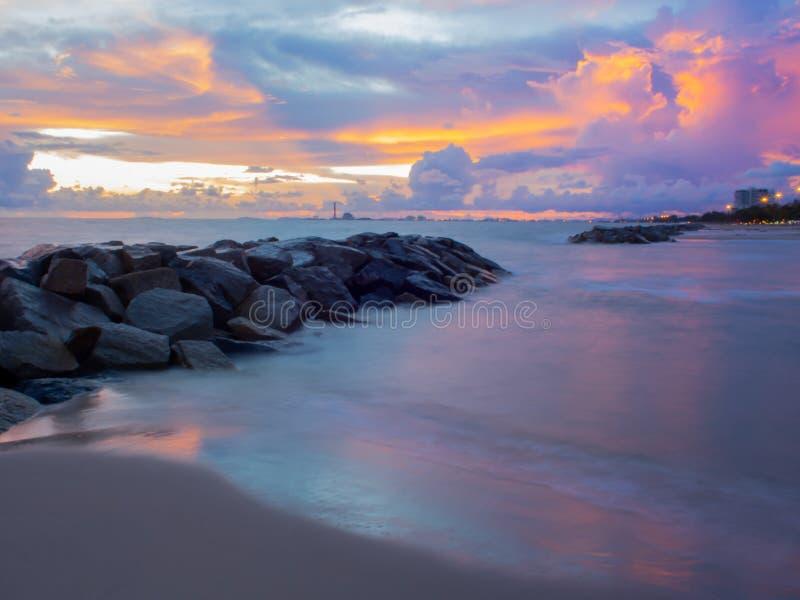 Πολλές πέτρες που συσσωρεύονται στη θάλασσα και σε ένα ζωηρόχρωμο υπόβαθρο ουρανού, ηλιοβασίλεμα στοκ εικόνες