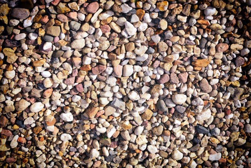 Πολλές πολύχρωμες μικρές πέτρες Υπόβαθρο με το σύντομο χρονογράφημα Σύσταση των χαλικιών θάλασσας στοκ εικόνες