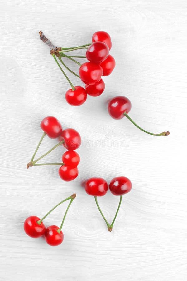 Πολλές προνύμφες των ώριμων, κόκκινων, κερασιών σε ένα άσπρο ξύλινο υπόβαθρο Τοπ όψη στοκ φωτογραφίες