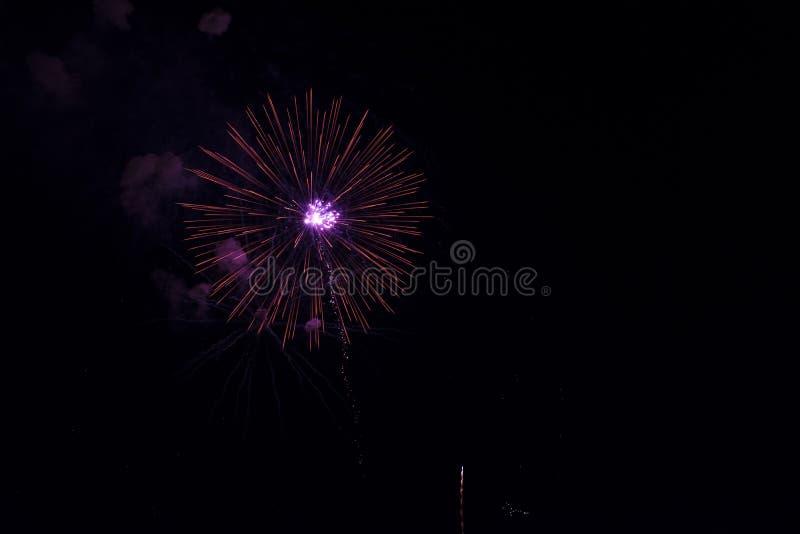 Πολλαπλάσια πυροτεχνήματα στο νυχτερινό ουρανό σε μια σύνθεση στο κόκκινο σκιών στοκ εικόνες