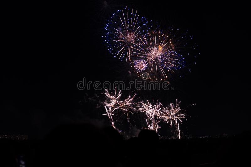 Πολλαπλάσια πυροτεχνήματα στο νυχτερινό ουρανό σε μια σύνθεση στις σκιές χρυσές και μπλε στοκ εικόνες με δικαίωμα ελεύθερης χρήσης