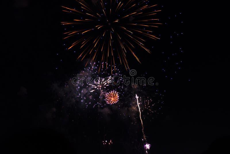 Πολλαπλάσια πυροτεχνήματα στο νυχτερινό ουρανό σε μια σύνθεση στις σκιές κόκκινες και χρυσές στοκ φωτογραφία