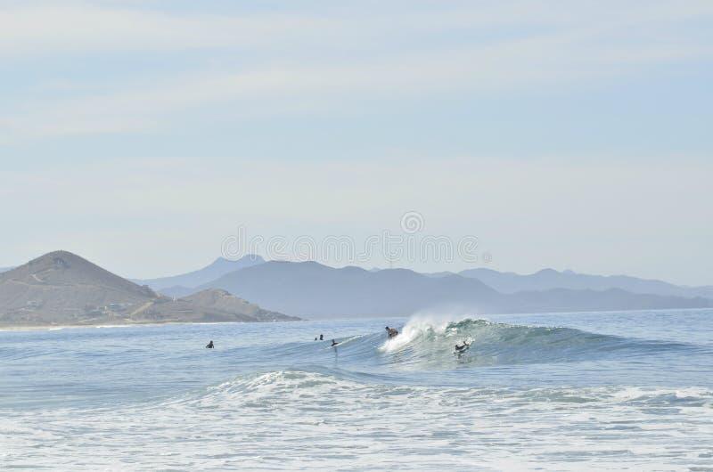 Πολλαπλάσια surfers που οδηγούν το κύμα μακριά του τοπίου Baja, Μεξικό ακτών στοκ φωτογραφίες με δικαίωμα ελεύθερης χρήσης