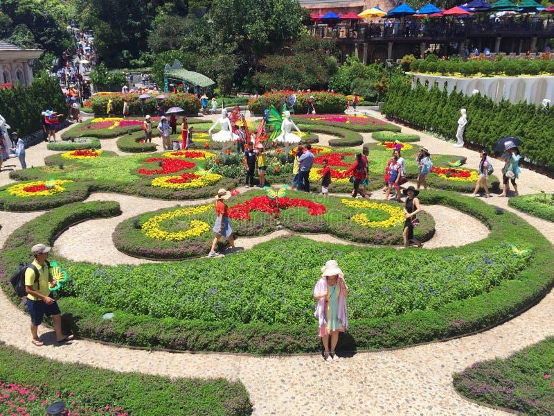 Πολλοί άνθρωποι παίρνουν τις φωτογραφίες σε έναν όμορφο κήπο λουλουδιών στοκ εικόνα