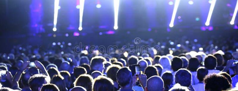 πολλοί άνθρωποι στη ζωντανή συναυλία με τα επίκεντρα στη σκηνή στοκ εικόνες