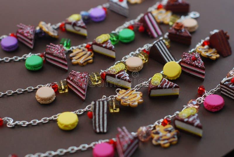 Πολλοί διαμορφώνουν τα βραχιόλια με τα μικροσκοπικά κέικ και τα επιδόρπια, τα μπισκότα και Macaroons Πολυμερής άργιλος Jewellry στοκ φωτογραφία με δικαίωμα ελεύθερης χρήσης