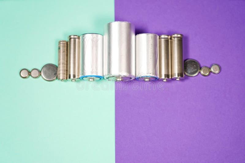 Πολλοί διαφορετικοί τύποι χρησιμοποιούμενοι ή νέα μπαταρία, επανακαταλογηστέος συσσωρευτής, αλκαλικές μπαταρίες στο υπόβαθρο χρώμ στοκ φωτογραφία με δικαίωμα ελεύθερης χρήσης