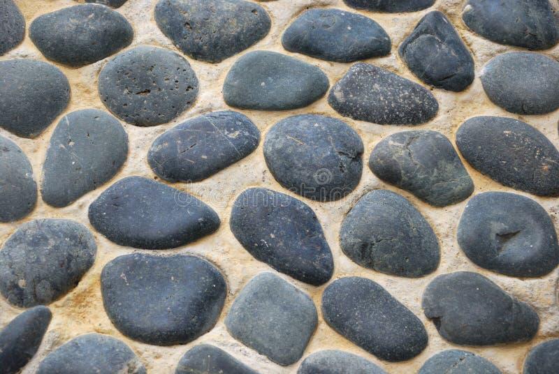 Πολλοί που τρίβουν τους βράχους στο πεζοδρόμιο στοκ εικόνες