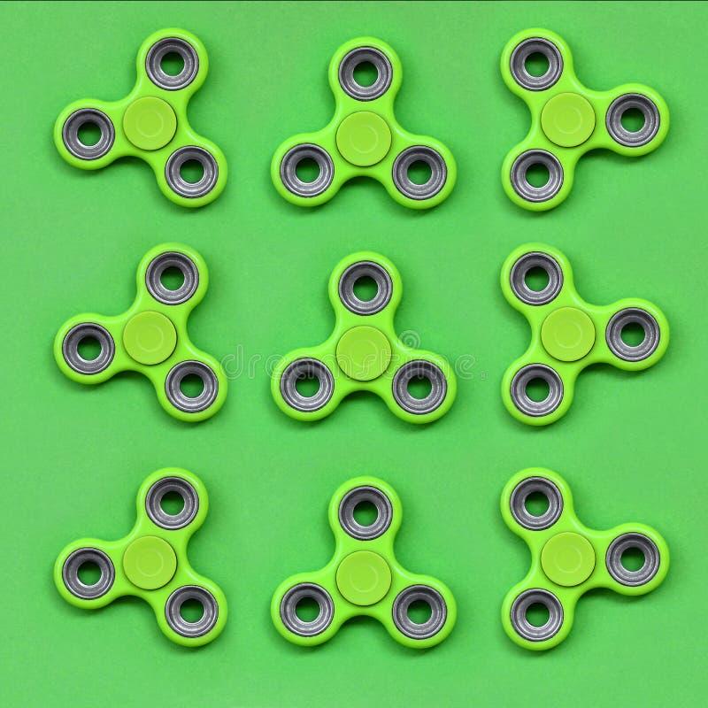 Πολλοί πράσινοι fidget κλώστες βρίσκονται στο υπόβαθρο σύστασης του πράσινου εγγράφου χρώματος κρητιδογραφιών μόδας στην ελάχιστη διανυσματική απεικόνιση