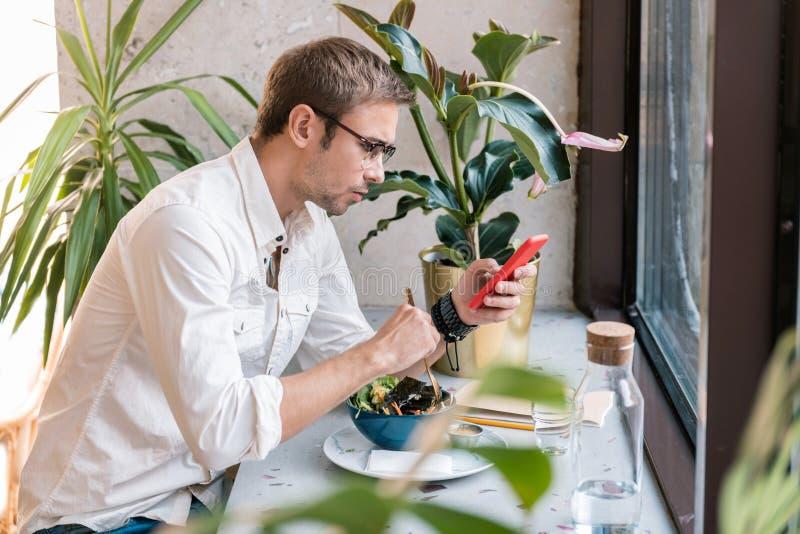 Πολυάσχολα επιτυχή μηνύματα ανάγνωσης επιχειρηματιών ενώ έχοντας το μεσημεριανό γεύμα στοκ φωτογραφία