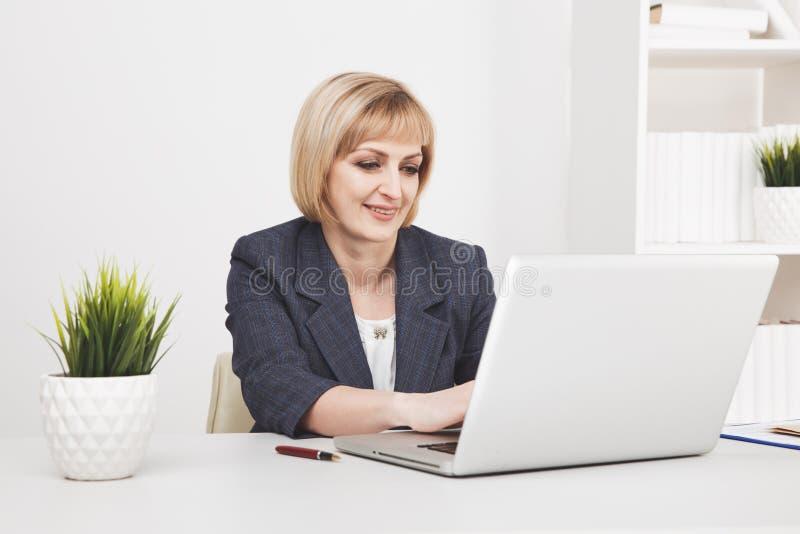 Πολυάσχολη γυναίκα γραμματέων στην αρχή Λειτουργώντας lap-top και τηλέφωνο στοκ φωτογραφία με δικαίωμα ελεύθερης χρήσης